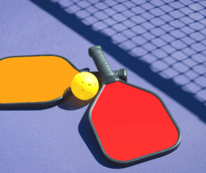Pickleball and Seniors - Two pickleball paddles and ball with shadow of net.