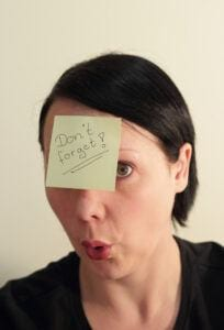 Woman With Posted Note on Forehead That Reads Don't Forget!