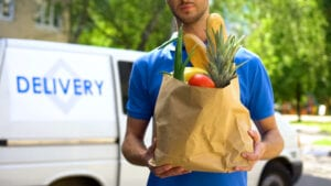 Food Delivery Service. Male holding grocery bag full of food.