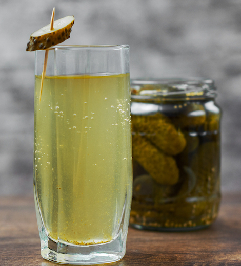 Pickle Juice Benefits- Pickle-Juice-in-a-Drinking Glass and a Jar of Pickles Together on a Wooden Table