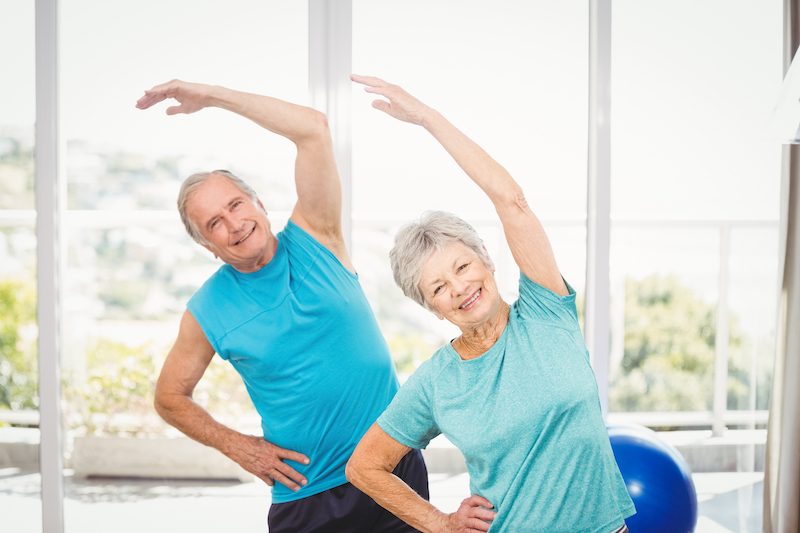 A senior man and woman stretching after exercising
