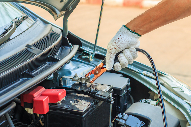Mechanic Using Battery Jumper Cables to Charge Dead Battery