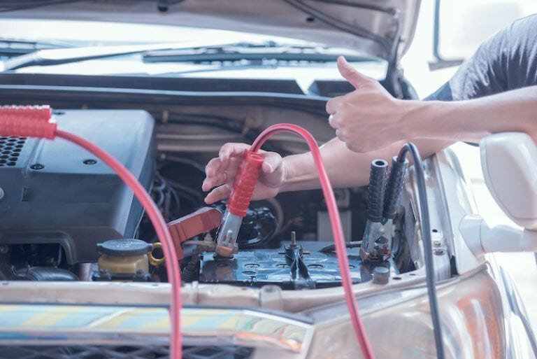 Car Battery Jump Starter -Person Uses Battery Jumper Cables For Jump Starting A Dead Battery