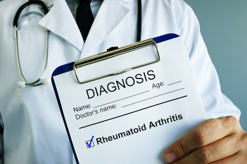 About Arthritis and Rheumatism - Doctor Holding Clipboard with Diagnosis Rheumatoid Arthritis Written