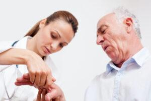 About Arthritis and Rheumatism-Nurse Checking Man's Hand Joints