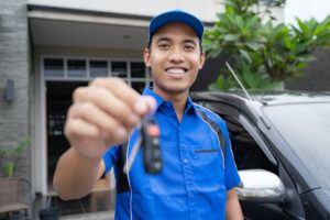 Car Battery Jump Starter - Mechanic Holding Car Key and Smiling