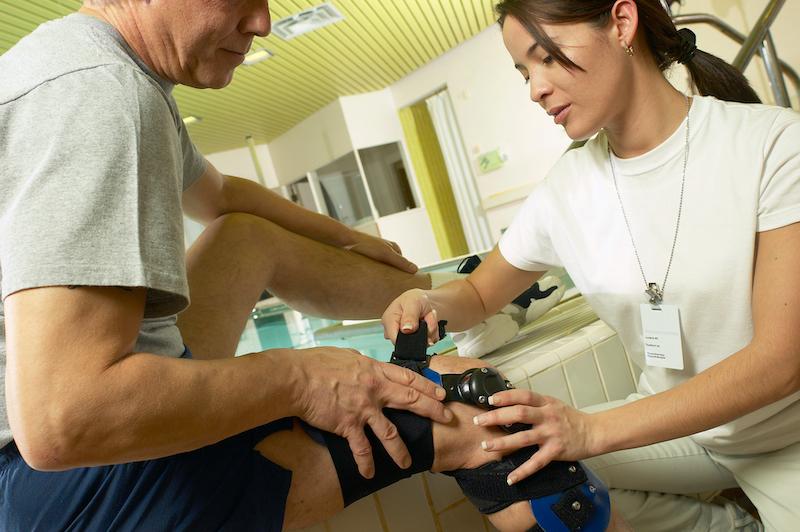 Woman Putting Knee Brace on a Man