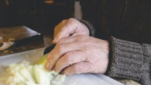 In Home Safety for the Elderly-Elderly Man Slicing and Onion